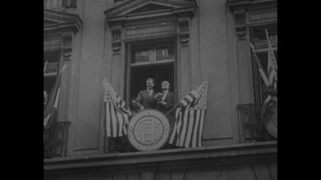 Pan huge throng of cheering people in Paris street / aviator Charles Lindbergh on balcony with US Ambassador to France Myron T Herrick Lindbergh...
