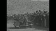 Pan hundreds of civilians in Western clothes stand in desert watching Southern Tunisia Army troops parade through sand / French Premier and War...