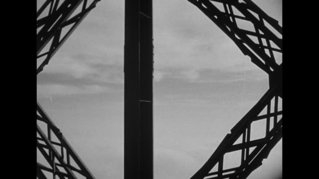 CU pan intricate framework of the Eiffel Tower / man and woman silhouetted ride up the Tower elevator / POV from the elevator of the framework of the...