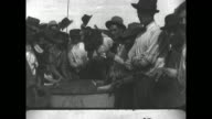 Pan IWW members rounded up in Bisbee Arizona wave their hats in refugee camp / group of IWW men stands at a camp water trough and one man washes his...