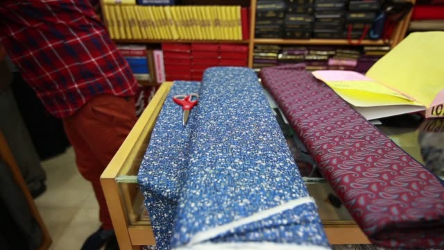 Pan L R MS Employees work at the Sams Tailor store MCS an employee cuts a length of fabric and folds it Low angle MWS Employees assist a customer at...