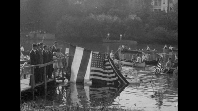 Pan left a military band plays as people shielded by trees listen / an American flag is pulled aside to reveal the Holland I submarine built by John...
