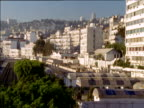 Pan left across city of white buildings over tree tops to trains in station and people on platforms Alger