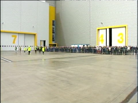 Pan left across crowd outside hangar watching as wing of Airbus A380 emerges on truck Toulouse; 05 Apr 04