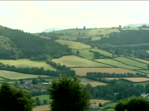 Pan left across hillsides and fields Powys