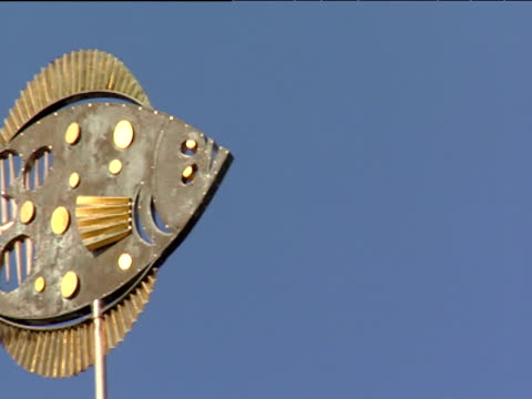 Pan left across ornate metal fish symbol for Hamburg fish market under clear blue sky