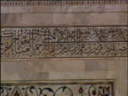 Pan left along Persian scripture from Koran on gateway to Taj Mahal Agra