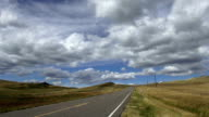 Pan left and right of wide angle 3/4 view of highway on prairie under puffy clouded blue sky