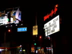 Pan left and tilt down from Whisky a Go Go club and illuminated Clarke Street sign to gas station Sunset Strip