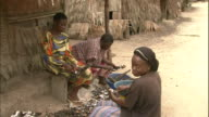 Pan left and zoom in to group of women shelling shellfish in rural village on Niger Delta, Kura region, Nigeria