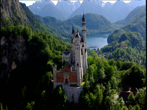 Pan left around Neuschwanstein castle surrounded by forested mountains with lakes and mountains in background Bavaria