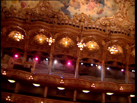 Pan left around ornate theater boxes painted ceilings and chandeliers
