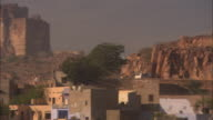 Pan left as car drives towards Mehrangarh Fort. Available in HD.
