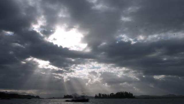 Pan left as clouds scud over coast.