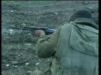 Pan left as crouched Russian soldier fires rifle along muddy road Jan 00
