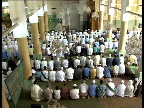 Pan left as Muslim men bow heads and pray whilst kneeling in mosque during Maulid celebrating birth of Prophet Mohammed Cairo