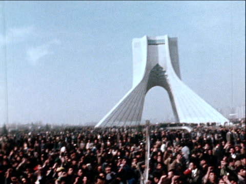 Pan left from Azadi Monument to large crowd of supporters waiting to see Ayatollah Khomeini following his return from exile Iran 1 February 1979