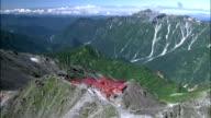 Pan left from lodge on top of mountain to surrounding mountain range, Mount Yarigatake, Nagano
