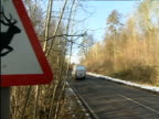 Pan left from road to road sign warning presence of deer