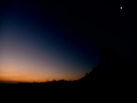 Pan left from silhouetted hill in orange and blue evening light half moon in sky