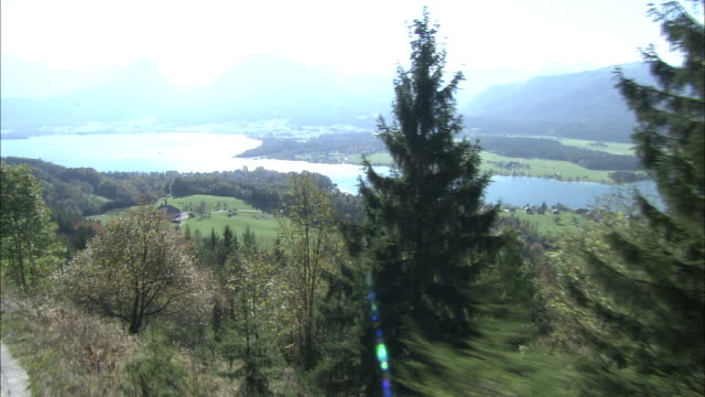Pan left from trees on mountainside overlooking Wolfgangsee to carriage and tracks of Schafberg mountain railway