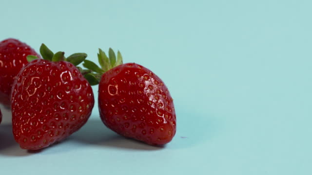Pan left onto, then off, a group of four strawberries arranged on a plain pale blue background.