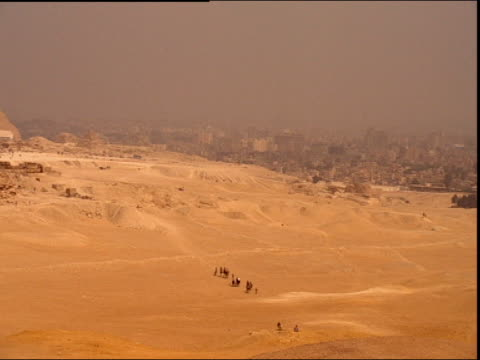 Pan left over desert landscape with pyramids and ruins Egypt