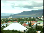 Pan left over Reykjavik rooftops and trees including houses church spires sea and mountains