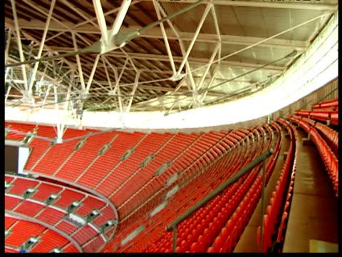 Pan left over seats from top tier of Wembley Stadium London