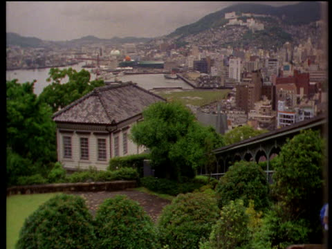 Pan left over skyline of Nagasaki harbour from colonial gardens of Glover House; rain falling in distance