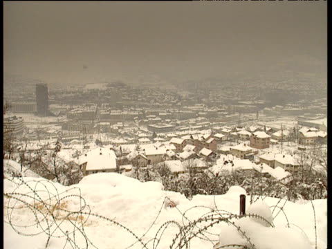 Pan left over snow covered houses in valley to back of UN soldier standing watch on hill Sarajevo 1995