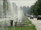 Pan left over traffic and gushing fountains on Unirii Boulevard Bucharest