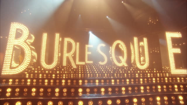 pan left to right of letters with lights on them that spell burlesque on stage. could be in theater or nightclub.