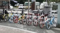 Pan left to right Ofo Inc bicycles Xiaoming Danche bicycles and Mobike bicycles and others stand parked on a sidewalk in Shanghai China on Thursday...