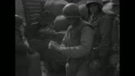 pan line of casual American soldiers wearing army issue winter clothing and helmets and duffel bags at rear / VS soldier examining a pair of thick...