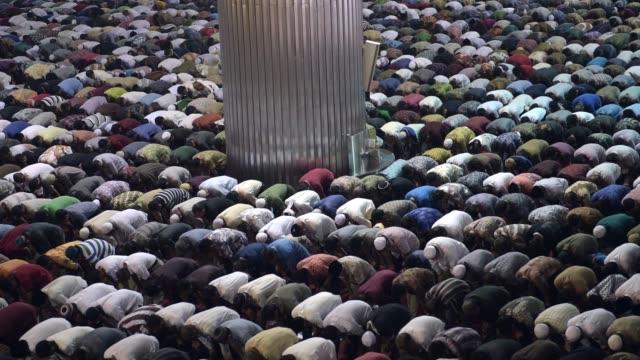 WS pan LR men praying in the hall