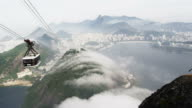 Pan of a gondola ride on a misty day over the Brazilian coastline in Rio de Janeiro, Brazil