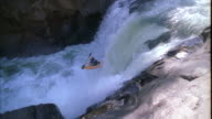 Pan of a kayaker falling down a waterfall in slow motion