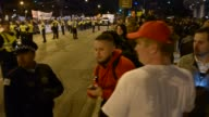 Pan Of Crowd And Two Men Reporting That They Had Been Assaulted While Harmonica Player Plays And Dances