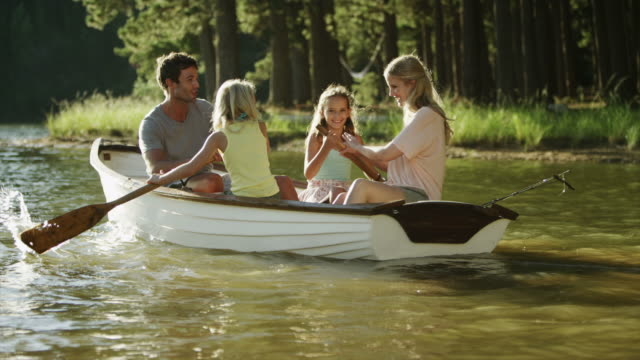 WS Pan of family rowing boat on lake