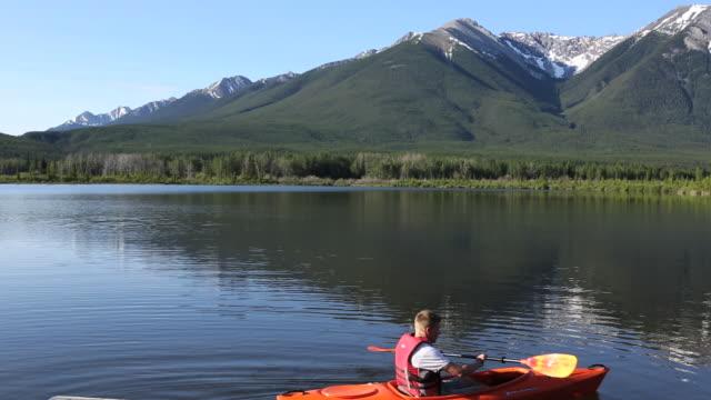 Pan of kayaker leaving dock edge, paddling into lake