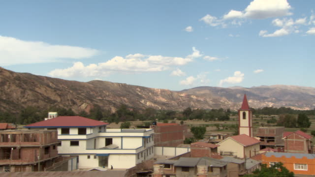 L-R Pan of mountains skirting Cochabamba, Bolivia, with residential areas and church steeple in view.