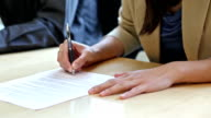 Pan of two people signing a contract