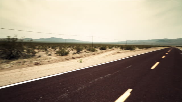 Pan over lonely desert road, mountains in distance