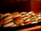 Pan over sandwiches in cafe and reflection of man looking at them through window, with stylised focus effect, London