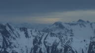 Pan over snow covered mountain tops at dusk.