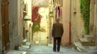 Pan rear view senior man with cane walking down steep village road / Biot, France