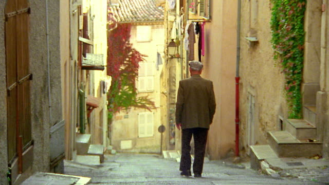 Pan rear view senior man with cane walking down steep village road / Biot, France