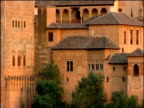 Pan right across Alhambra fortification to valley below Granada Spain