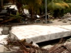 MS pan right across damage to houses caused by tsunami, Maldives